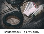 Small photo of handcuffs and narcotic on a wooden background