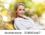 Small photo of people, beauty and relaxation concept - beautiful young woman in white bath robe lying on chaise-longue and drinking champagne at spa over holidays lights background