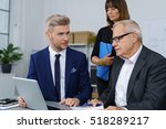 three workers at desk using... | Shutterstock . vector #518289217