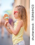 Small photo of Adorable little girl eating ice-cream outdoors at summer. Cute kid enjoying real italian gelato near Gelateria in Rome