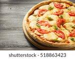 margarita pizza at wooden table | Shutterstock . vector #518863423
