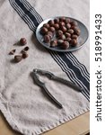 Small photo of A metal nutcracker and a vintage pewter plate with whole hazelnuts. linen kitchen towel.