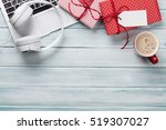 Small photo of Christmas gift boxes, laptop, headphones and coffee cup on wooden background. Top view with copy space for your text