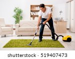 man cleaning home with vacuum... | Shutterstock . vector #519407473
