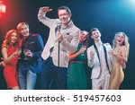 Small photo of Stand-up comedy and party. Showman with microphone. Group of cheerful friends toasting with wineglasses among confetti.