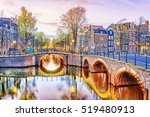 Stock photo traditional dutch old houses and bridges on canals in amsterdam at night netherlands 519480913