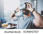 Stock photo bearded man wearing virtual reality goggles in modern coworking studio smartphone using with vr 519893707