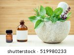 Small photo of Alternative health care and herbal medicine .Fresh herbs and aromatic oil with mortar and pestle on wooden background. Various herbs rosemary ,sage ,sweet basil leaves and green mint branch.