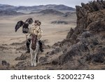 Small photo of Kazakh Eagle Hunter in traditionally trained golden eagles riding horse in a desert mountain. Ol-gei,Western Mongolia.