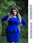 Small photo of Young beautiful plus size model in blue dress outdoors with arms akimbo, xxl woman on nature, professional makeup and hairstyle