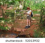 Small photo of Lady Hiker leaning on a fence in a woodland glade reading a map