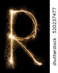 Small photo of English big Letter R made from burning sparkles on black background. Shiny festive party firework font, latin alphabet text sign.