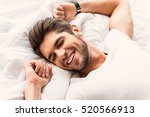 happy man sleeping in bedroom | Shutterstock . vector #520566913
