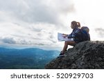 Small photo of woman sitting on mountain and open a map,adventure travel, vintage effect tone.