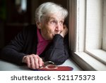 An Elderly Woman Looks Sadly...