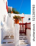 Small photo of Classical Greek white staircase with a pots of flowers - typical architecture in Islands