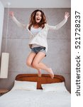 Small photo of Portrait of a young happy woman jumping on bed at home