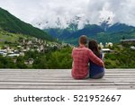 Small photo of Young couple in love sitting on the roof and admire the scenery
