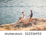 Stock photo couple of guys playing with their dog on the mountain near ocean romantic time in nature with 522536953