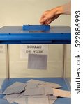 Small photo of Blue Ballot box of french republic and hand voting with mention of vote place in the background