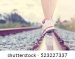 Female Legs In Sneakers On The...