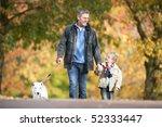 Stock photo man with young son walking dog through autumn park 52333447