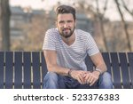 Small photo of Young happy adult man sitting on a bench, looking at camera, smirking. Wearing t-shirt, and jeans.