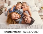 Small photo of Happy parents and kids enjoying their morning in bed