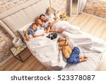 family sleeping together on bed | Shutterstock . vector #523378087