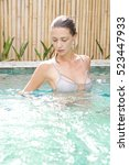 young woman relaxing in the pool | Shutterstock . vector #523447933