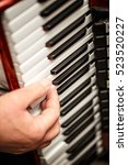 Small photo of Closeup detail of hands playing an accordion instrument