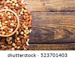 mixed nuts in a bowl on wooden... | Shutterstock . vector #523701403