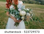 Red Haired Bride Holding A...