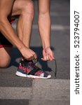 Small photo of Sport exercise, fitness, workout. Young athlete, runner tie shoelaces in shoes. Outdoor activity, endurance. Active person road training. Healthy lifestyle.