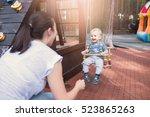 mom swinging baby boy in swing... | Shutterstock . vector #523865263