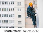 Small photo of Industrial climber in helmet and uniform puttying wall on height. Risky job. Extreme work. Worker alpinist.
