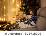 Small photo of Cute sweet child, boy, playing on mobile phone under the blanket on first advent Sunday, christmas tree behind them
