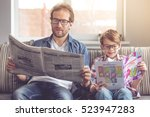 father and son are reading... | Shutterstock . vector #523947283