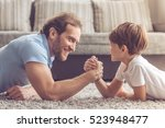 father and son are wrestling... | Shutterstock . vector #523948477