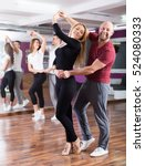 Small photo of Positive adult couples enjoying of partner dance and smiling indoor