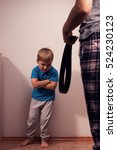 Small photo of Angry mother with belt and little child in corner. Domestic violence, aggression on the family. Abuse against children.