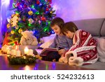 Small photo of Two sweet children, boy brothers, reading a book under the blanket on first advent Sunday, christmas tree behind them