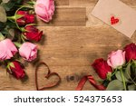 roses  and red ribbon on wooden