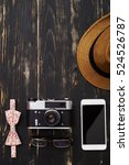 Small photo of Top view of stylish man table mockup - hat, vintage camera, eyeglasses, smartphone and floral ornamentation bowtie on dark wooden background