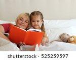 happy small girl lying in bed...   Shutterstock . vector #525259597