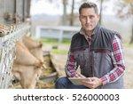 farmer in barn using digital... | Shutterstock . vector #526000003