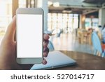 Stock photo mockup image of hand holding white mobile phone with blank white screen and silver laptop on 527014717