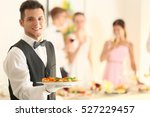 Handsome young waiter with...