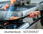chef doing flambe to food in... | Shutterstock . vector #527243527