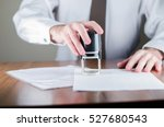 Small photo of Notary public in office stamping document,vertical photo